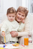 Cute small girl is painting with her grandparent Stock Images