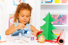 Cute small girl paints New Year ball for Xmas tree. Cute small girl painting New Year ball for Christmas tree while sitting alone at the white table with Stock Photography