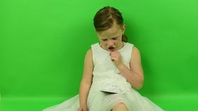 Cute small girl reads e-book on chroma key background. Little girl dressed in a romantic dress. White wedding dress stock video