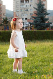 Cute small girl standing in grass. Wearing white Royalty Free Stock Image