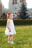 Cute small girl standing in grass. Wearing white Stock Images