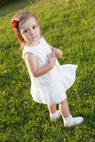 Cute small girl standing in grass. Wearing white and looking at camera Royalty Free Stock Photos