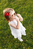 Cute small girl standing in grass. Wearing white and sun glasses Stock Photo