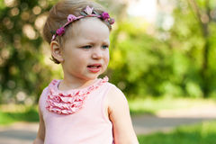 Cute small girl in the summer park. Stock Photos