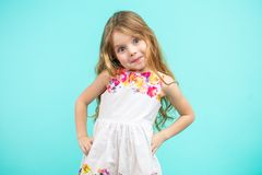 Cute small girl wearing a flowers summer dress isolated on blue. Cute small girl wearing a flowers summer dress with arms akimbo isolated on blue royalty free stock photography