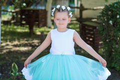 Cute small girl wearing a white and blue dress posing over nature background, child with a wreath of artificial flowers on her he Royalty Free Stock Photography