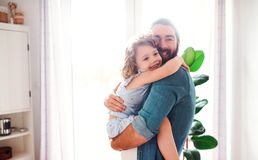 A small girl with young father at home, hugging. A cute small girl with young father at home, hugging royalty free stock image