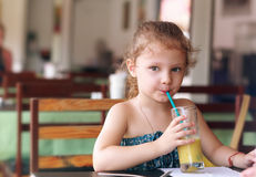 Cute small kid girl drinking juice in cafe Stock Images
