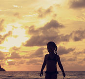 Cute small kid girl walking alone on the beach on bright beautif Royalty Free Stock Photo