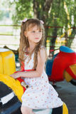 Cute small little girl riding a colorful carousel Royalty Free Stock Photography