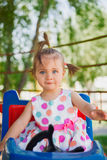 Cute small little girl riding a colorful carousel Royalty Free Stock Photo