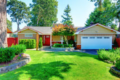Cute small rambler house with red door and white garage door. Stock Photo