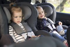 Cute small twins in car seats in the car stock images