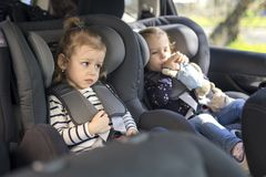 Cute small twins in car seats in the car royalty free stock photos