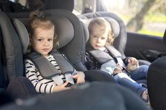 Cute small twins in car seats in the car stock photos