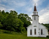White Country Church in Wisconsin. A cute, small, white country church in Wisconsin. The arched windows and steeple remind us of days gone by royalty free stock photography