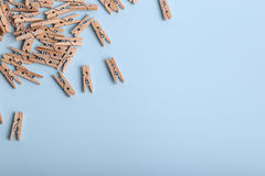 Cute small wooden clothes pegs on a Blue background Royalty Free Stock Photo