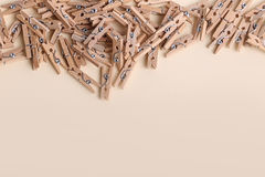 Cute small wooden clothes pegs on a cream background Royalty Free Stock Image