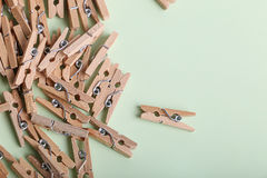 Cute small wooden clothes pegs on a green background Royalty Free Stock Images