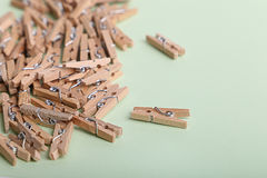 Cute small wooden clothes pegs on a green background Stock Photo