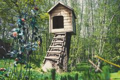 Cute small wooden dogs House in a garden with stairs. Cute small wooden dog& x27;s House in a garden with stairs with flowers little cottage old whelp dog-home stock photography