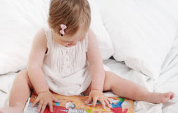 Cute smart baby girl exploring her book, child education Royalty Free Stock Photo
