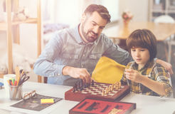 Cute smart boy learning to play chess royalty free stock photo