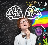 Cute smart child boy on blackboard background with maths formula and art pattern. Brainstorming, creativity and education concept.  stock photos