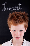 Cute and smart kid. In front of blackboard royalty free stock photography