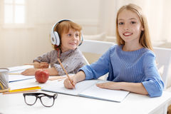 Cute smart siblings studying together Stock Photo