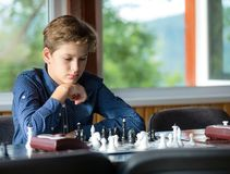 Cute, smart, 11 years old boy in shirt sits in the classroom and plays chess on the chessboard. Training, lesson, hobby, education stock image