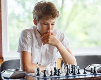 Cute, smart, 11 years old boy in white shirt sits in the classroom and plays chess on the chessboard. Training, lesson, hobby royalty free stock images