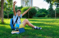 Cute, smart, young boy in blue shirt sits on the grass with globe, workbooks, chalkboard and holds his hands up in the park stock photography