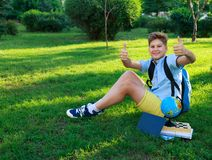 Cute, smart, young boy in blue shirt sits on the grass next to his school backpack, globe, chalkboard, workbooks. Education. Back to school concept royalty free stock photo