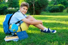 Cute, smart, young boy in blue shirt sits on the grass next to his school backpack, globe, chalkboard, workbooks. Education. Back to school concept royalty free stock photography