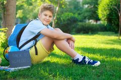 Cute, smart, young boy in blue shirt sits on the grass next to his school backpack, globe, chalkboard, workbooks. Education. Back to school concept royalty free stock images