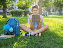 Cute, smart, young boy in blue shirt sits on the grass next to his school backpack, globe, chalkboard, workbooks. Education. Back to school concept stock photography
