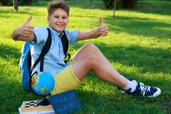 Cute, smart, young boy in blue shirt sits on the grass next to his school backpack, globe, chalkboard, workbooks. Education stock photo
