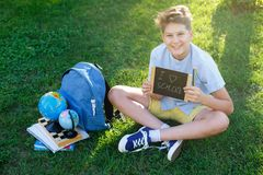 Cute, smart, young boy in blue shirt sits on the grass next to his school backpack, globe, chalkboard, workbooks. Education. Back to school concept royalty free stock photos