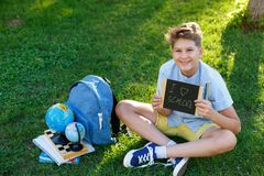 Cute, smart, young boy in blue shirt sits on the grass next to his school backpack, globe, chalkboard, workbooks. Education. Back to school concept stock photo