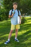 Cute, smart, young boy in blue shirt stands on the grass with globe and school backpack, workbooks. Education, back to school. Concept royalty free stock image