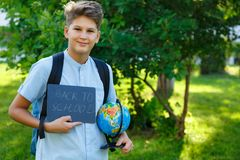 Cute, smart, young boy in blue shirt stands on the grass with globe and school backpack, workbooks. Education, back to school stock photo