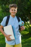 Cute, smart, young boy in blue shirt stands on the grass with globe and school backpack, workbooks. Education, back to school stock image