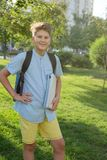 Cute, smart, young boy in blue shirt stands with workbooks on the grass in the park. Education, back to school stock photography