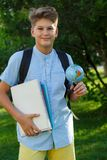 Cute, smart, young boy in blue shirt stands with workbooks on the grass in the park. Education, back to school stock photos