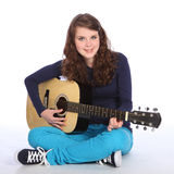 Cute smile by teenager girl on acoustic guitar. Lovely cute smile from pretty teenager girl with bright blue eyes, sitting on floor playing music on acoustic Royalty Free Stock Photos