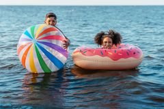 cute smiling african american brother and sister having fun with beach ball and swimming tube stock photo