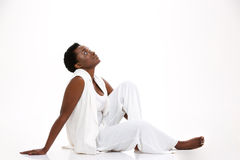 Cute smiling african american young woman sitting and looking up. Cute smiling african american young woman sitting on the floor and looking up over white stock photo