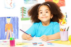 Cute smiling African girl writing at the desk. While sitting in playroom with wall behind which is full of kids drawings stock photo
