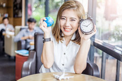 Cute smiling asia girl with globe and alarm clock stock photography